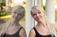 Attraktive blonde Frau reflektierte sich in einem Glasfenster Stockfotografie