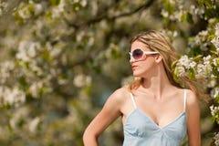 Attraktive blonde Frau unter blühendem Baum Stockbild