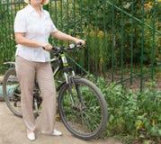 Attraktive blonde Frau von mittlerem Alter auf einem Fahrrad im Park Stockfotografie