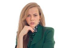 Attraktive blonde Geschäftsdame in der grünen Uniform, welche die Kamera mit heiklem flüchtigem Blick betrachtet Stockbild