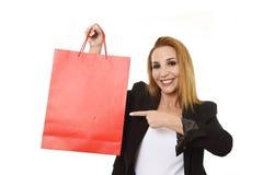 Attraktive blonde Geschäftsfrau, die das rote Einkaufstaschelächeln glücklich und erfüllt im Verkaufskonzept hält Lizenzfreie Stockfotografie
