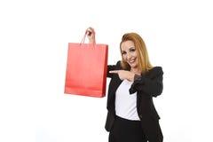 Attraktive blonde Geschäftsfrau, die das rote Einkaufstaschelächeln glücklich und erfüllt im Verkaufskonzept hält Stockbilder