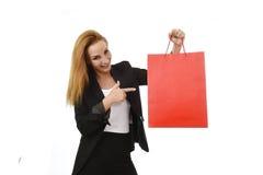 Attraktive blonde Geschäftsfrau, die das rote Einkaufstaschelächeln glücklich und erfüllt im Verkaufskonzept hält Stockfotografie