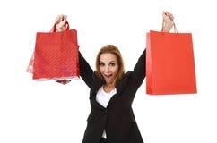 Attraktive blonde Geschäftsfrau, die das rote Einkaufstaschelächeln glücklich und erfüllt im Verkaufskonzept hält Stockfotos
