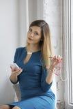 Attraktive blonde Geschäftsfrau hält Gläser und das Schauen zur Kamera Stockfoto