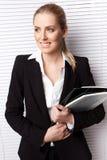 Attraktive blonde Geschäftsfrau mit Datei Lizenzfreie Stockfotografie