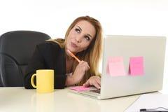 Attraktive blonde Geschäftsfrau 40s, die an der BüroLaptop-Computer arbeitet Stockfoto
