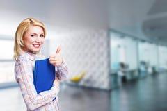 Attraktive blonde Geschäftsfrau vor einer Büroszene Stockbild