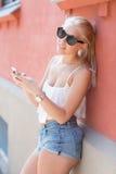 Attraktive blonde Jugendliche, die Smartphone verwendet Stockbild