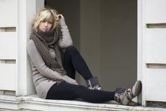 Attraktive blonde junge Frau auf Fensterbrett Stockbilder