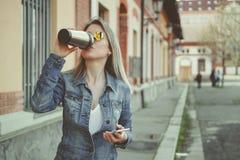 Attraktive blonde junge Frau, die auf die Straße, unter Verwendung ihres Smartphone und trinkenden Kaffees geht Lizenzfreie Stockbilder