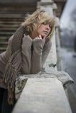 Attraktive blonde junge Frau, die auf Marmorbaluster sich lehnt Lizenzfreie Stockfotos