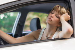 Attraktive blonde junge Frau, die in einem Auto schläft Lizenzfreie Stockbilder