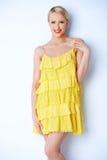 Attraktive blonde junge Frau, die im gelben Kleid aufwirft Stockfoto