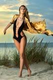 Attraktive blonde junge Frau im Badeanzug mit sexy Körper auf dem Strand Lizenzfreie Stockfotos