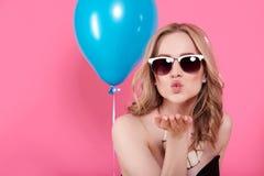 Attraktive blonde junge Frau im eleganten Partykleid und im goldenen Schmuck Geburtstag feiernd und einen Kuss in Richtung zur Ka Lizenzfreies Stockfoto