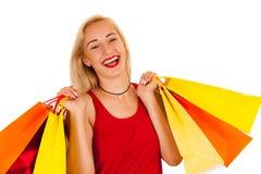 Attraktive blonde junge Frau mit den Einkaufstaschen lokalisiert Lizenzfreie Stockfotografie
