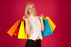 Attraktive blonde junge Frau mit den Einkaufstaschen lokalisiert Lizenzfreies Stockfoto