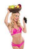 Attraktive blonde lächelnde Frau im rosa Badeanzug, der Trauben und Korb mit Früchten hält Lizenzfreie Stockbilder