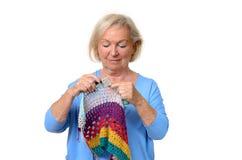 Attraktive blonde ältere Dame, die ihr Stricken tut Lizenzfreie Stockfotos