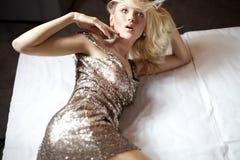 Attraktive blonde Schönheit, die im Goldkleid aufwirft Lizenzfreies Stockbild