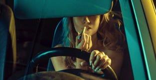 Attraktive blonde Schönheit unter Verwendung des Lippenstifts in einem Auto Stockbild