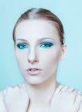 Attraktive blonde schulterfreie Frau mit dunklem Auge bilden