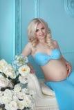 Attraktive blonde schwangere Frau, die ihren Bauch mit den Händen, p berührt Lizenzfreie Stockbilder