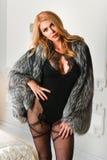 Attraktive blonde sexy Frau, die im schwarzen Wäschebodysuit und im Luxuspelzmantel aufwirft Stockfotos