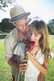 Attraktive blonde smeling Rosen, die mit Partner stehen Stockfotografie