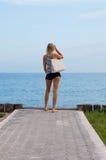 Attraktive blonde Stellung auf dem Strand Lizenzfreie Stockfotografie