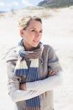 Attraktive blonde Stellung auf dem Strand im woolen Schal Lizenzfreies Stockfoto