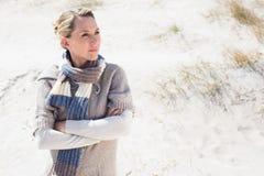 Attraktive blonde Stellung auf dem Strand im woolen Schal Lizenzfreie Stockfotos