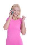 Attraktive blonde Studentin, die auf dem Mobile lokalisiert flirtet Stockbild