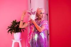 Attraktive blonde vorbildliche Stellung über rosa Hintergrund lizenzfreie stockfotos