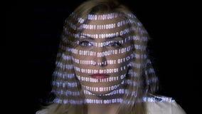 Attraktive blonde weibliche Computerarbeitskraft, die durch binär Code, während digitale, sich scheuert Daten auf ihrem Gesicht p stock footage