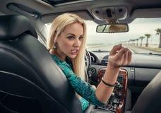 Attraktive blonde weibliche emotionale Gespräche zum hinterer Sitzpassagier Stockbild