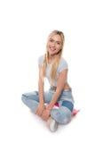 Attraktive Blondine, die auf Skateboard sitzen und an der Kamera lokalisiert auf Weiß lächeln Stockfotografie