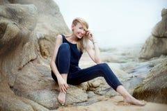 Attraktive Blondine, die auf Steinen aufwerfen Lizenzfreie Stockfotografie