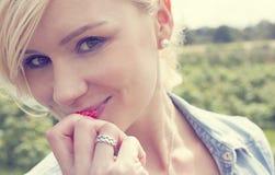 Attraktive Blondine, die eine reife Erdbeere genießt Lizenzfreie Stockbilder
