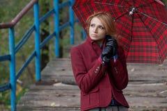 Attraktive Blondine, die unter einem roten Regenschirm aufwerfen Stockfotografie