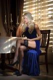 Attraktive Blondine im eleganten langen Kleid, das nahe einer Tabelle in einem luxuriösen klassischen Innenraum sitzt Herrliches  Stockbild