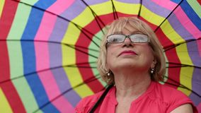 Attraktive Blondine mit buntem Regenschirm stock video