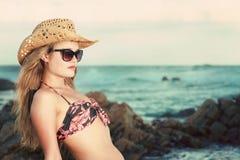 Attraktive Blondine mit dem Hut und Sonnenbrille, die sich rückwärts lehnen Lizenzfreie Stockfotos