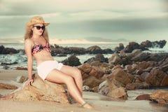 Attraktive Blondine mit dem Hut und Sonnenbrille, die sich rückwärts lehnen Lizenzfreie Stockfotografie