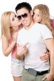 Attraktive Blondine zwei, die jungen Mann küßt Stockfotografie