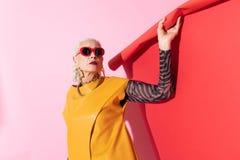 Attraktive Blondinestellung über rosa Hintergrund stockfotografie