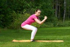 Attraktive braune behaarte Frauentrainingshinterteile und Beinmuskeln in der Hocke Lizenzfreie Stockbilder