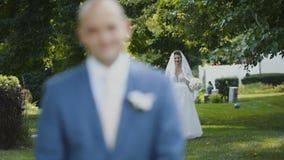 Attraktive Braut mit dem faszinierenden Blumenstrauß, der zu einem Bräutigam im grünen Park geht stock video