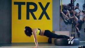 Attraktive brunette Frau in den Gamaschen, in der gelben Spitze und in den Turnschuhen führt Übungen auf TRX-Schleifen, Bügel in  stock video
